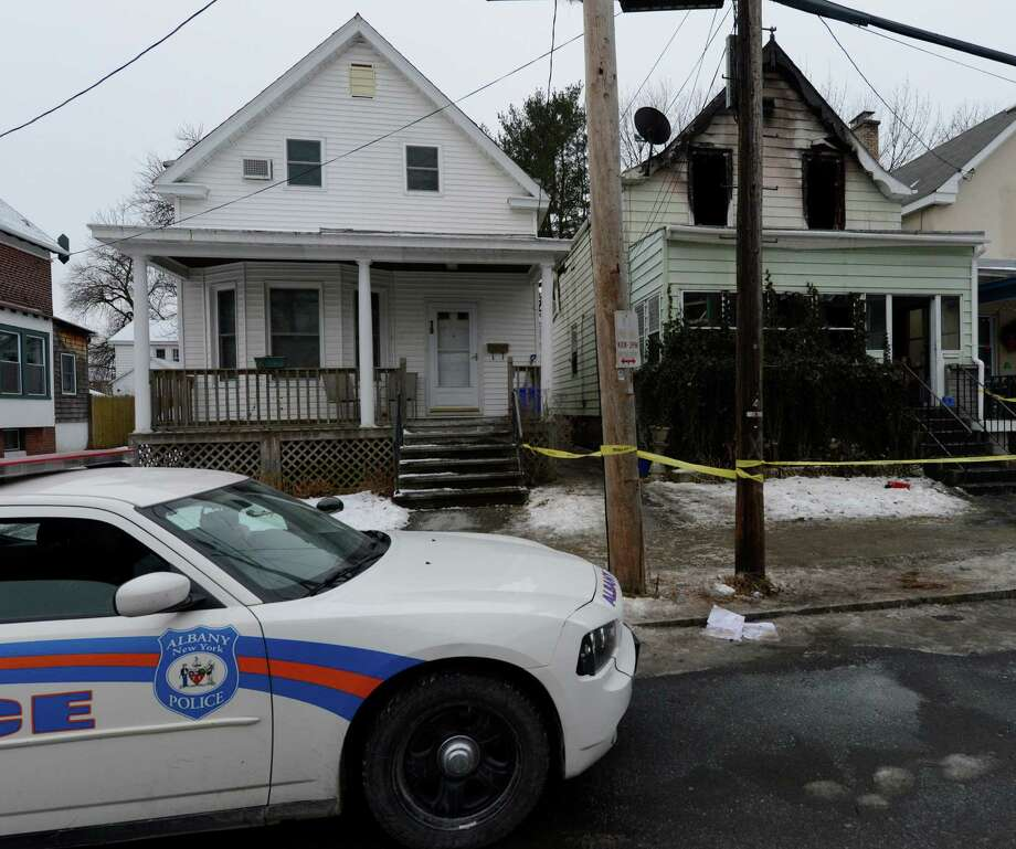 An Albany Police officer sits outside of 12 Arcadia Avenue Jan. 28, 2013 after a fire struck the home in Albany, N.Y.  A body was found in the building after the fire was put out prompting the police presence.  (Skip Dickstein/Times Union) Photo: SKIP DICKSTEIN / 00020930A