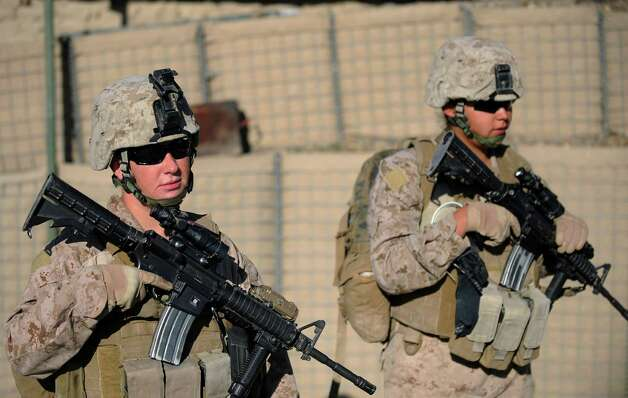 A female US Marine corporal patrols alongside a male Marine during a patrol in Afghanistan. A reader says males in the military will face a dilemma as how to treat women in combat with all the conflicting societal and military attitudes, plus the differences in the male and female psyches.  Photo: AFP/Getty Images / AFP ImageForum