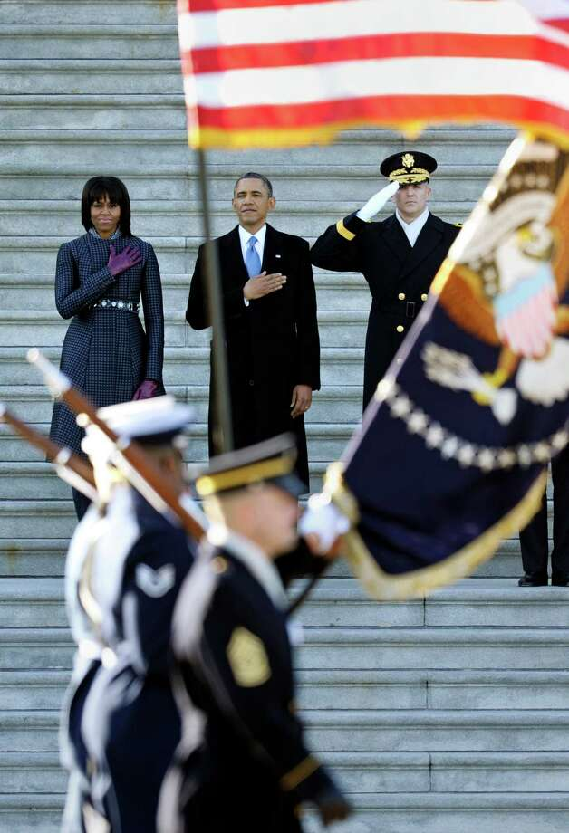 President Barack Obama, first lady Michelle Obama  and Army Maj. Gen. Michael Linnington salute a military honor guard at the inaugural parade. Military from across the country served as inaugural detail. Photo: Cliff Owen, Associated Press / FR170079 AP