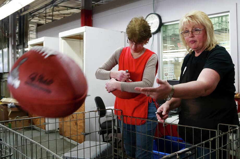 Barb Ulrey, left, and Pam Clark, right, inspect official game balls for the NFL football Super Bowl XLVII at Wilson Sporting Goods Co. in Ada, Ohio, Monday, Jan. 21, 2013. The San Francisco Forty Niners will play the Baltimore Ravens in the Super Bowl on Feb. 3 in New Orleans. (AP Photo/Rick Osentoski) Photo: Rick Osentoski, ASSOCIATED PRESS / AP2013