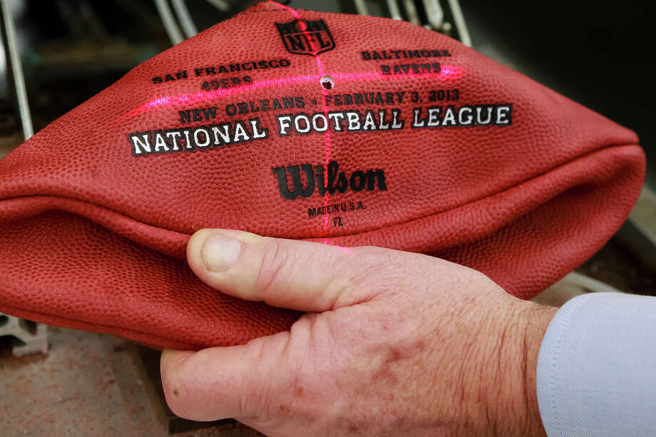 A laser is used to lineup an official game ball for the NFL football Super Bowl XLVII so the team names can be branded onto it at Wilson Sporting Goods Co. in Ada, Ohio, Monday, Jan. 21, 2013. The San Francisco Forty Niners will play the Baltimore Ravens in the Super Bowl on Feb. 3 in New Orleans. (AP Photo/Rick Osentoski) Photo: Rick Osentoski, ASSOCIATED PRESS / AP2013