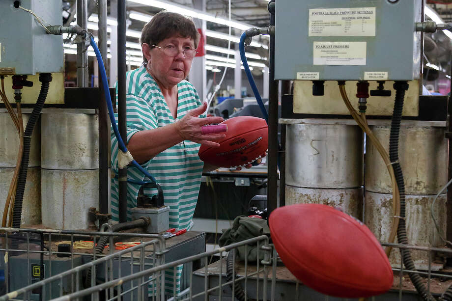 Deb Conley tosses a finished official game ball for the NFL football Super Bowl XLVII into a bin to wait final inspection at Wilson Sporting Goods Co. in Ada, Ohio, Monday, Jan. 21, 2013. The San Francisco Forty Niners will play the Baltimore Ravens in the Super Bowl on Feb. 3 in New Orleans. (AP Photo/Rick Osentoski) Photo: Rick Osentoski, ASSOCIATED PRESS / AP2013