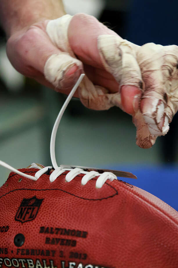 Doug Falkhauser laces up an official game ball for the NFL football Super Bowl XLVII at Wilson Sporting Goods Co. in Ada, Ohio, Monday, Jan. 21, 2013. The San Francisco Forty Niners will play the Baltimore Ravens in the Super Bowl on Feb. 3 in New Orleans. (AP Photo/Rick Osentoski) Photo: Rick Osentoski, ASSOCIATED PRESS / AP2013