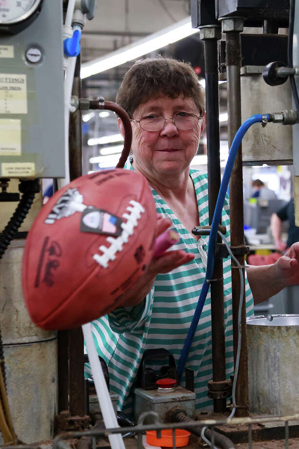 Deb Conley tosses a finished official game ball for the NFL football Super Bowl XLVII into a bin to wait final inspection at Wilson Sporting Goods Co. in Ada, Ohio, Monday, Jan. 21, 2013.  (AP Photo/Rick Osentoski) Photo: Rick Osentoski, ASSOCIATED PRESS / AP2013