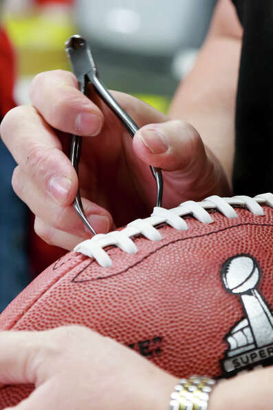 Pam Clark inspects an official game ball for the NFL football Super Bowl XLVII at Wilson Sporting Go
