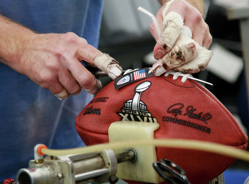 Doug Falkhauser laces up an official game ball for the NFL football Super Bowl XLVII at Wilson Sport