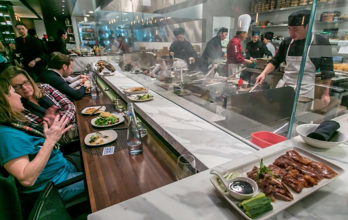 You watch the red- or black-jacketed cooks in the exhibition kitchen, surrounded by a smoky fog of hot woks.