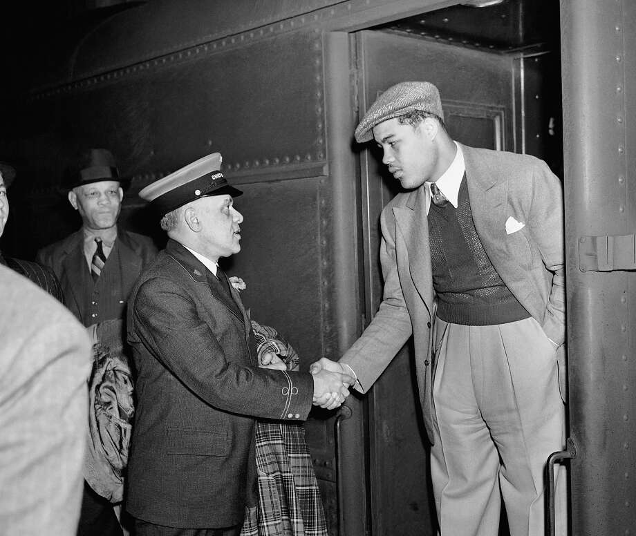 Joe Louis, heavyweight champ, breezed into Grand Central Station, at New York City, May 11, 1938 in sports clothes and cap.   He came to New York to sign up to fight Max Schmeling at Yankee Stadium June 22, 1938   Here he gets the grip of friendship from Jim Williams, chief porter and the nation's original redcap. Photo: Anonymous, AP / 1938 AP