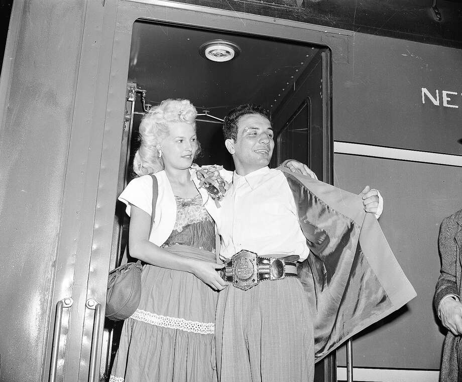 The newly crowned World Middleweight Boxing Champion Jake LaMotta, accompanied by his wife Vicky, arrives from Detroit, where he defeated French World Champion Marcel Cerdan, at Grand Central Terminal in 1949. Photo: ASSOCIATED PRESS / AP1949