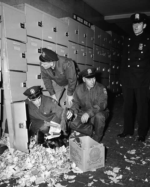 Police examine debris after an explosion blew one locker apart and damaged three other lockers in Ne