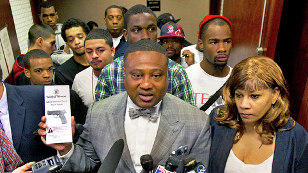 Quanell X, center, stands with Trey Foster's mom, Don, right, after his appearance in the 228th State District Court at the Harris County Criminal Courthouse Monday, Jan. 28, 2013, in Houston. Authorities took Trey Foster, 22, into custody Friday, as a suspect in the shooting that took place on Lone Star College's campus. Quanell X stated that Foster had a receipt purchasing the gun and that he took a concealed handgun class although he didn't obtain a concealed carrying license.