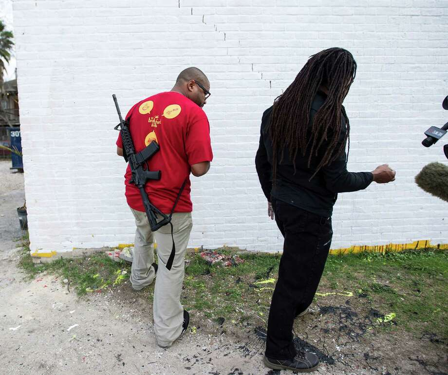 Marcus Davis, owner of The Breakfast Klub and Artist Reginald Adams look over the damage in front of his building at the corner of Travis and Alabama, Monday, Jan. 28, 2013, in Houston. Overnight, vandals threw paint on the Barack Obama mural, defacing it. Adams got a text about 7am this morning and immediately white washed the wall.  Plans are for another mural to go up in the next few weeks.  Davis has a permit to carry a gun and says that by carrying the gun, it sends a message that just because people disagree with each other, they don't' have to resort to acts that will do harm. Photo: Karen Warren, Houston Chronicle / © 2013 Houston Chronicle