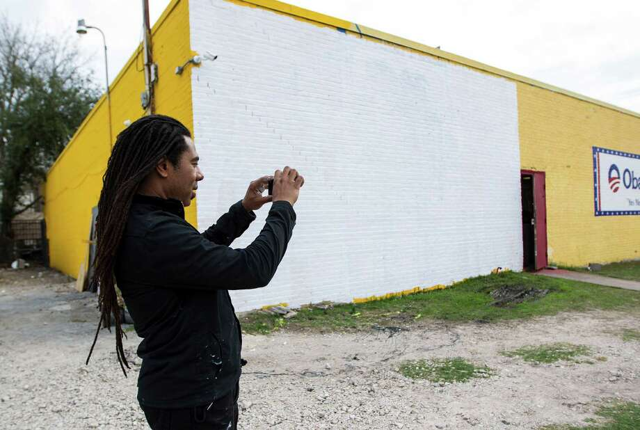 Artist Reginald Adams takes a photo in front of the white washed wall which formerly was his mural of Barack Obama on one of the The Breakfast Klub building at the corner of Travis and Alabama, Monday, Jan. 28, 2013, in Houston. Overnight, vandals threw paint on the Barack Obama mural, defacing it. Adams got a text about 7am this morning and immediately white washed the wall.  Plans are for another mural to go up in the next few weeks. Photo: Karen Warren, Houston Chronicle / © 2013 Houston Chronicle