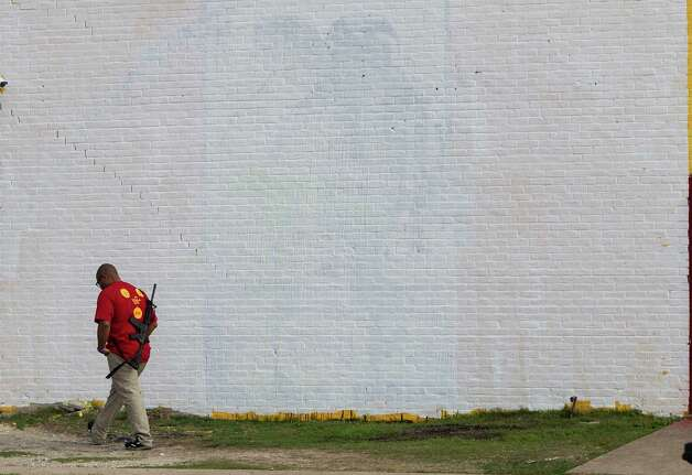 Marcus Davis, owner of The Breakfast Klub, walks by the area that was a mural of Barak Obama on The Breakfast Klub's building at the corner of Travis and Alabama, Monday, Jan. 28, 2013, in Houston. Overnight, vandals threw paint on the mural, defacing it. Artist Reginald Adams got a text about 7am, and he then came over and white washed the wall.  Plans are for another mural to go up in the next few weeks.  Davis has a permit to carry a gun and says that by carrying the gun, it sends a message that just because people disagree with each other, they don't' have to resort to acts that will do harm. Photo: Karen Warren, Houston Chronicle / © 2013 Houston Chronicle