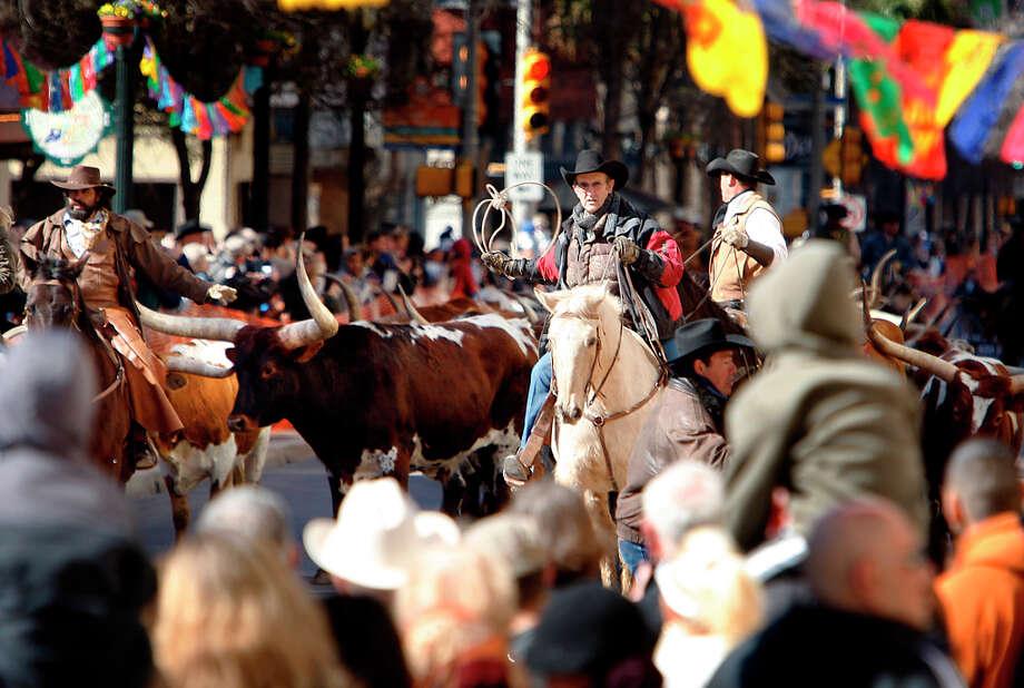 Cowboys guide 40 head of Longhorn cattle down Houston Street in 2010. Photo: Kin Man Hui, SAN ANTONIO EXPRESS-NEWS / San Antonio Express-News