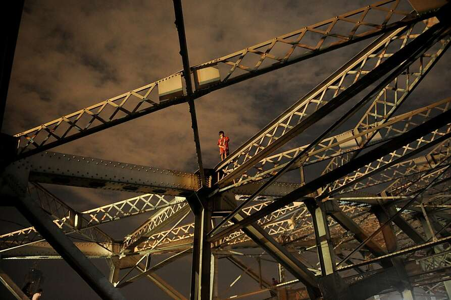 Do you know where your children are, Manila? A boy stands on one of the trusses of the Quezon