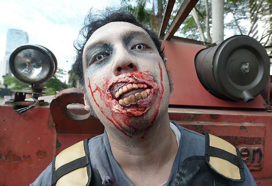 "Big smile now, let's see those pearly whites:A zombie in Jakarta stands for a photo before marching to ""raise awareness of cleanness"" and collect donations for residents affected by recent flooding. Photo: Adek Berry, AFP/Getty Images"