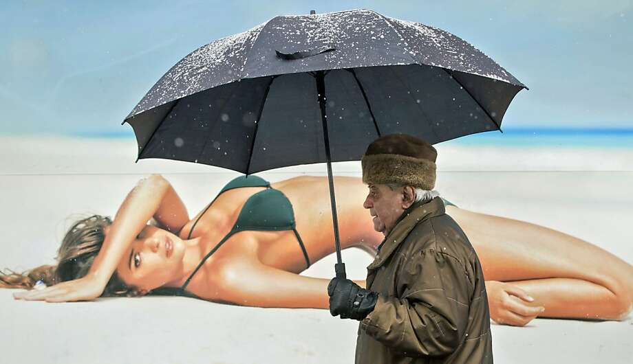 An elderly man walks holding an umbrella, during a snowfall, back dropped by a large poster in Bucharest, Romania, Monday, Jan. 28, 2013. (AP Photo/Vadim Ghirda) Photo: Vadim Ghirda, Associated Press