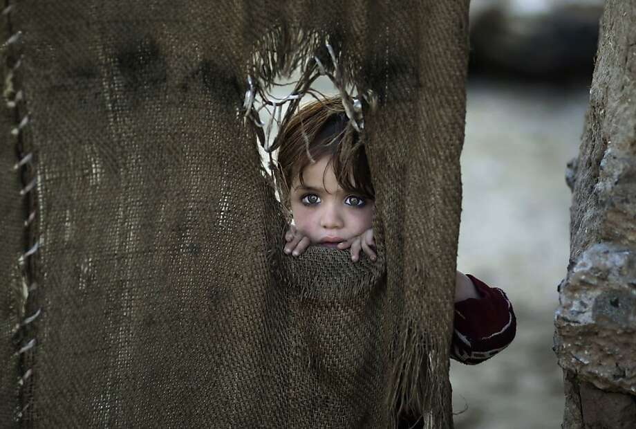 Peephole person: A young Pakistani girl peeks through the hole of a tattered curtain that serves as the door to her family's home in an Islamabad slum. She and her family fled Pakistan's tribal areas due to fighting between militants and the army. Photo: Muhammed Muheisen, Associated Press