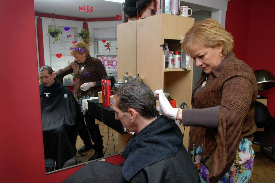 Brenda Cerezo, owner of Cerezo New Image Salon on Hope St in Stamford, Conn., works in her salon coloring customer Steve Smith's hair on Monday January 28, 2013. Photo: Dru Nadler / Stamford Advocate Freelance
