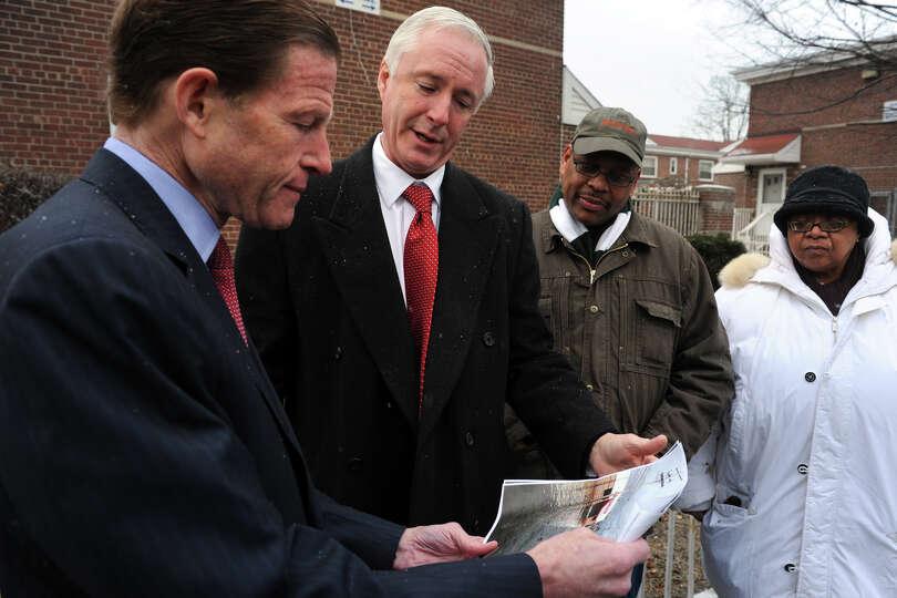 Senator Richard Blumenthal and Mayor Bill Finch look at photos of flooding at Marina Village during