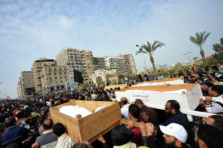 Egyptian mourners carry the coffins of six people killed in clashes the day before, during their funeral in Port Said, on January 28, 2013. President Mohamed Morsi sought to crack down on violence which has swept Egypt since January 26 in which more than 45 people have died after a Cairo court handed down death sentences on 21 supporters of a local football club, Al-Masry, in the wake of football violence in 2012. Morsi declared a month-long state of emergency in the provinces of Port Said, Suez and Ismailiya. AFP PHOTO / STR Photo: -, AFP/Getty Images / 2013 AFP