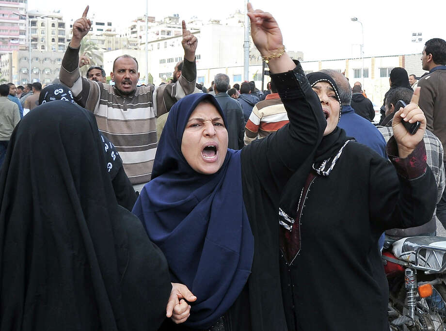 Egyptian female mourners shout during the funerals of six people killed in clashes the day before, in Port Said, on January 28, 2013. President Mohamed Morsi sought to crack down on violence which has swept Egypt since January 26 in which more than 45 people have died after a Cairo court handed down death sentences on 21 supporters of a local football club, Al-Masry, in the wake of football violence in 2012. Morsi declared a month-long state of emergency in the provinces of Port Said, Suez and Ismailiya. AFP PHOTO / STR Photo: -, AFP/Getty Images / 2013 AFP