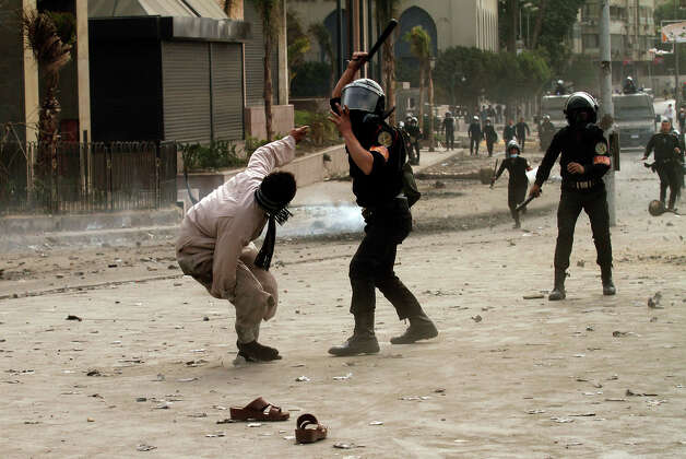 "An Egyptian riot policeman hits a protester during clashes near Cairo's Tahrir Square on January 28, 2013. Egypt's cabinet approved a draft law that would allow President Mohamed Morsi to deploy the armed forces on the streets ""to participate with the police in preserving security and protecting vital establishments."" AFP PHOTO/MOHAMMED ABED Photo: MOHAMMED ABED, AFP/Getty Images / 2013 AFP"