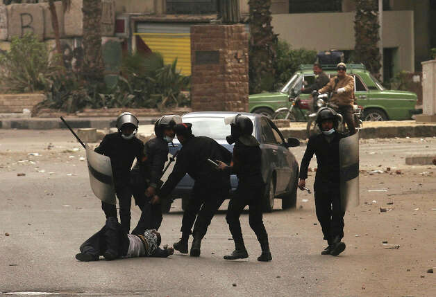 "Egyptian riot policemen drag a protester along the ground during clashes near Cairo's Tahrir Square on January 28, 2013. Egypt's cabinet approved a draft law that would allow President Mohamed Morsi to deploy the armed forces on the streets ""to participate with the police in preserving security and protecting vital establishments."" AFP PHOTO/MOHAMMED ABED Photo: MOHAMMED ABED, AFP/Getty Images / 2013 AFP"