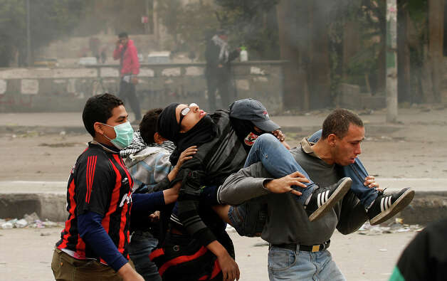 "Egyptians protesters carrying a wounded youth during clashes near Cairo's Tahrir Square on January 28, 2013. Egypt's cabinet approved a draft law that would allow President Mohamed Morsi to deploy the armed forces on the streets ""to participate with the police in preserving security and protecting vital establishments."" AFP PHOTO/MOHAMMED ABED Photo: MOHAMMED ABED, AFP/Getty Images / 2013 AFP"