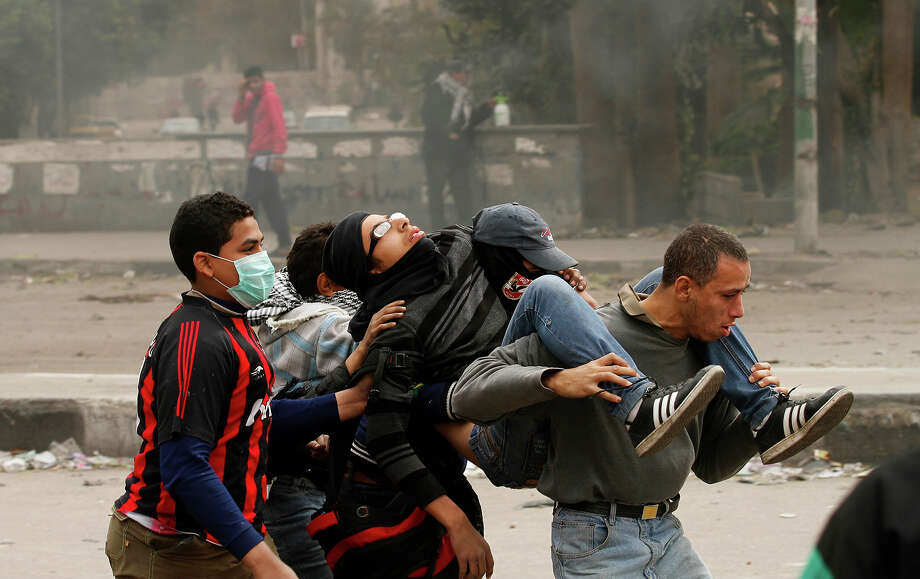 """Egyptians protesters carrying a wounded youth during clashes near Cairo's Tahrir Square on January 28, 2013. Egypt's cabinet approved a draft law that would allow President Mohamed Morsi to deploy the armed forces on the streets """"to participate with the police in preserving security and protecting vital establishments."""" AFP PHOTO/MOHAMMED ABED Photo: MOHAMMED ABED, AFP/Getty Images / 2013 AFP"""