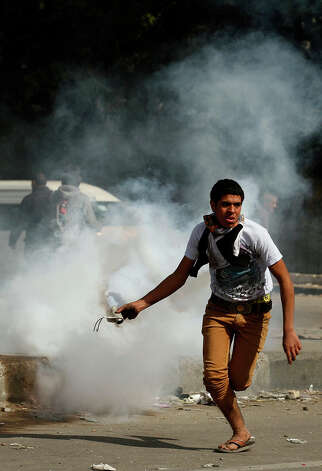 "An Egyptian protester prepares to throw back a tear gas canister fired by riot police during clashes near Cairo's Tahrir Square on January 28, 2013. Egypt's cabinet approved a draft law that would allow President Mohamed Morsi to deploy the armed forces on the streets ""to participate with the police in preserving security and protecting vital establishments."" AFP PHOTO/MOHAMMED ABED Photo: MOHAMMED ABED, AFP/Getty Images / 2013 AFP"