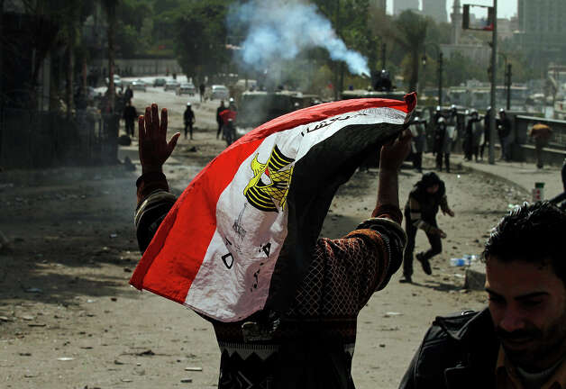 "An Egyptian protester waves his national flag as he gestures towards riot police during clashes near Cairo's Tahrir Square on January 28, 2013. Egypt's cabinet approved a draft law that would allow President Mohamed Morsi to deploy the armed forces on the streets ""to participate with the police in preserving security and protecting vital establishments."" AFP PHOTO/MOHAMMED ABED Photo: MOHAMMED ABED, AFP/Getty Images / 2013 AFP"