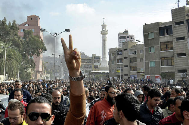 An Egyptian mourner flashes the sign for victory as mourners march in the canal city of Port Said on January 28, 2013 during the funeral of six people killed in clashes the day before, which were triggered after a court sentenced 21 people to death over a football riot that killed more than 70 people last year. A state of emergency came into force in three Egyptian provinces Port Said, Suez and Ismailiya which have been hit by deadly rioting, as President Mohamed Morsi scrambled to contain deepening divisions with calls for a national dialogue. AFP PHOTO / STR Photo: AFP, AFP/Getty Images / 2013 AFP