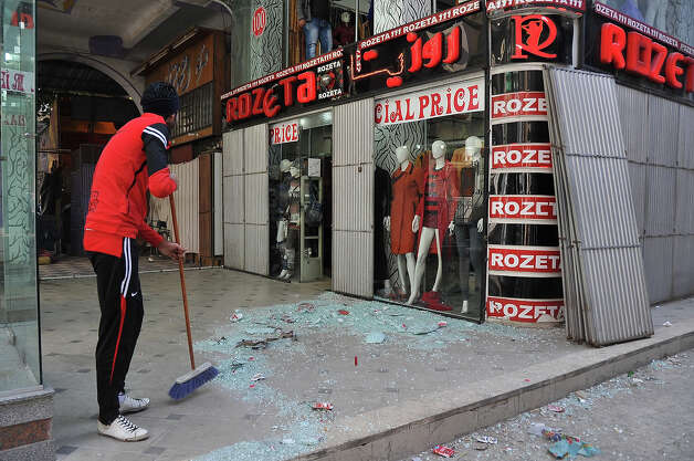 An Egyptian man sweeps shattered glass in front of shops in the canal city of Port Said on January 28, 2013 following clashes the day before, which were triggered after a court sentenced 21 people to death over a football riot that killed more than 70 people last year. A state of emergency came into force in three Egyptian provinces Port Said, Suez and Ismailiya which have been hit by deadly rioting, as President Mohamed Morsi scrambled to contain deepening divisions with calls for a national dialogue. AFP PHOTO / STR Photo: AFP, AFP/Getty Images / 2013 AFP