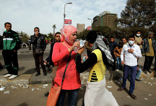 "An Egyptian protester pours water on the eyes of a victim suffering from exposure to tear gas during clashes with riot police near Cairo's Tahrir Square on January 28, 2013. Egypt's cabinet approved a draft law that would allow President Mohamed Morsi to deploy the armed forces on the streets ""to participate with the police in preserving security and protecting vital establishments."" AFP PHOTO/MOHAMMED ABED Photo: MOHAMMED ABED, AFP/Getty Images / 2013 AFP"