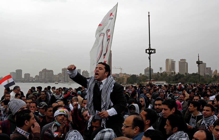 "An Egyptian protester shouts anti-Muslim Brotherhood slogans during a demonstration near Cairo's Tahrir Square on January 28, 2013. Egypt's cabinet approved a draft law that would allow President Mohamed Morsi to deploy the armed forces on the streets ""to participate with the police in preserving security and protecting vital establishments."" AFP PHOTO/MOHAMMED ABED Photo: MOHAMMED ABED, AFP/Getty Images / 2013 AFP"