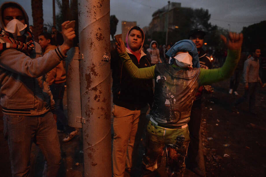 Egyptian protesters hit a lamp post with stones as a warning signal to fellow demonstrators during clashes with riot police near Cairo's Tahrir Square on January 28, 2013. Egypt's main opposition bloc rejected an invitation by President Mohamed Morsi for talks on the violence and political turmoil sweeping the country and instead called for fresh mass demonstrations. AFP PHOTO / KHALED DESOUKI Photo: KHALED DESOUKI, AFP/Getty Images / 2013 AFP