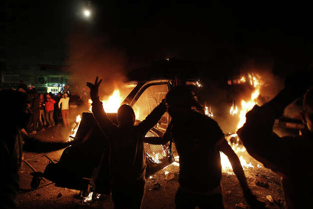 An Egyptian protester flashes victory signs near a police vehicle on fire in Cairo's Tahrir Square on January 28, 2013. Egypt's main opposition bloc rejected an invitation by President Mohamed Morsi for talks on the violence and political turmoil sweeping the country and instead called for fresh mass demonstrations. AFP PHOTO/MOHAMMED ABED Photo: MOHAMMED ABED, AFP/Getty Images / 2013 AFP