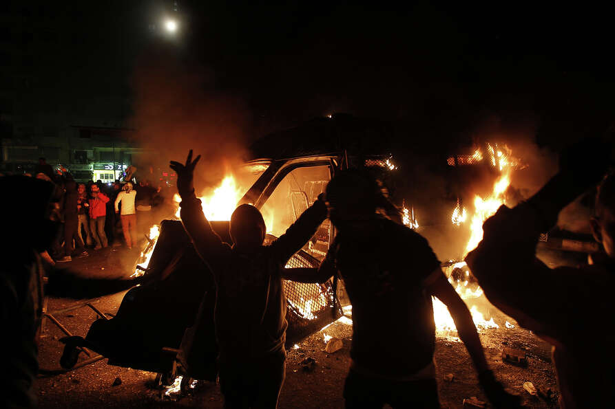 An Egyptian protester flashes victory signs near a police vehicle on fire in Cairo's Tahrir Square o