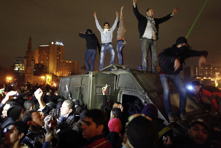 Egyptian protesters stand on a police vehicle before they set it on fire in Cairo's Tahrir Square on January 28, 2013. Egypt's main opposition bloc rejected an invitation by President Mohamed Morsi for talks on the violence and political turmoil sweeping the country and instead called for fresh mass demonstrations. AFP PHOTO / MAHMOUD KHALED Photo: AFP, AFP/Getty Images / 2013 AFP