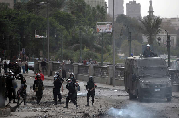 Egyptian riot police clash with protesters, not seen, near Tahrir Square, Cairo, Egypt, Monday, Jan. 28, 2013. Health and security officials say a protester has been killed in clashes between rock-throwing demonstrators and police near Tahrir Square in central Cairo. The officials say the protester died Monday on the way to the hospital after being shot. (AP Photo/Khalil Hamra) Photo: Khalil Hamra, ASSOCIATED PRESS / AP2013