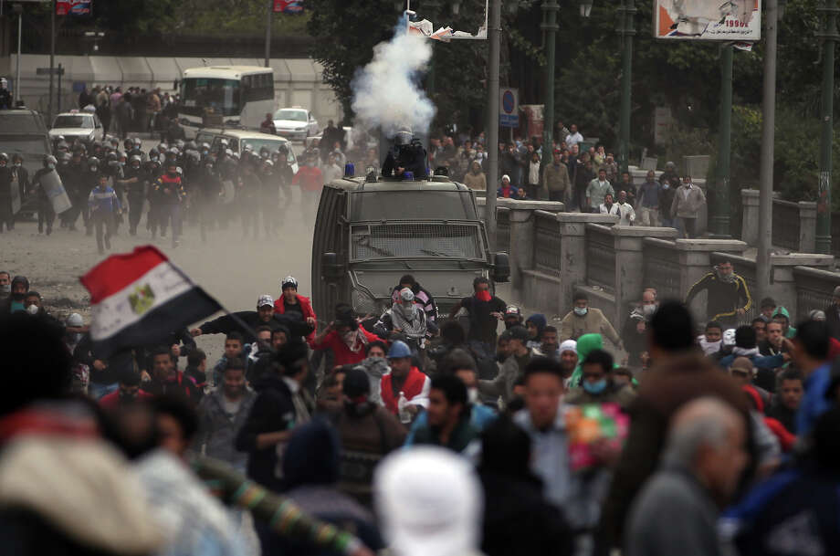 Egyptian protesters clash with riot police, background, near Tahrir Square, Cairo, Egypt, Monday, Jan. 28, 2013. Health and security officials say a protester has been killed in clashes between rock-throwing demonstrators and police near Tahrir Square in central Cairo. The officials say the protester died Monday on the way to the hospital after being shot. (AP Photo/Khalil Hamra) Photo: Khalil Hamra, ASSOCIATED PRESS / AP2013