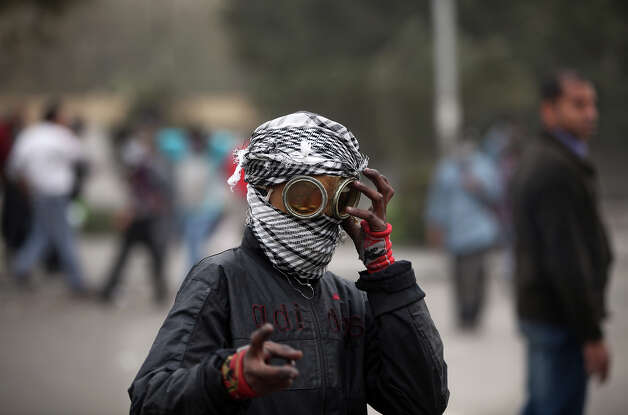An Egyptian protester covers his face during clashes with riot police, not seen, near Tahrir Square, Cairo, Egypt, Monday, Jan. 28, 2013. Health and security officials say a protester has been killed in clashes between rock-throwing demonstrators and police near Tahrir Square in central Cairo. The officials say the protester died Monday on the way to the hospital after being shot. (AP Photo/Khalil Hamra) Photo: Khalil Hamra, ASSOCIATED PRESS / AP2013