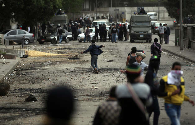 Egyptian protesters throw stones at riot police, background, during clashes near Tahrir Square, Cairo, Egypt, Monday, Jan. 28, 2013. Health and security officials say a protester has been killed in clashes between rock-throwing demonstrators and police near Tahrir Square in central Cairo. The officials say the protester died Monday on the way to the hospital after being shot. (AP Photo/Khalil Hamra) Photo: Khalil Hamra, ASSOCIATED PRESS / AP2013