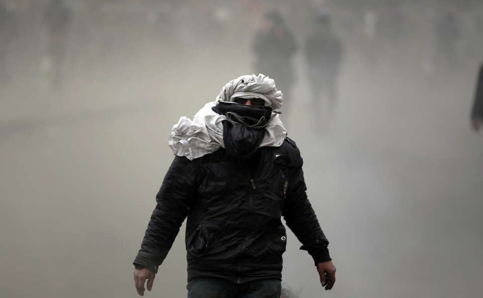 An Egyptian Protester covers his face during clashes with riot police, not seen, near  Tahrir Square