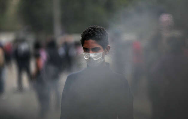 An Egyptian protester wears a mask during clashes with riot police, not seen, near Tahrir Square, Cairo, Egypt, Monday, Jan. 28, 2013. Health and security officials say a protester has been killed in clashes between rock-throwing demonstrators and police near Tahrir Square in central Cairo. The officials say the protester died Monday on the way to the hospital after being shot. (AP Photo/Khalil Hamra) Photo: Khalil Hamra, ASSOCIATED PRESS / AP2013