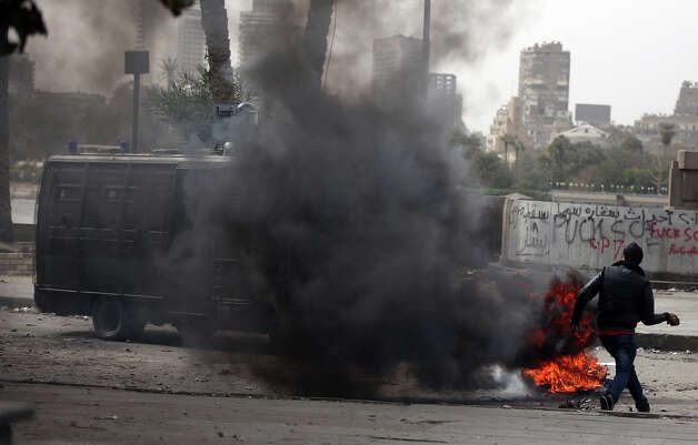 An Egyptian protester throws stones at riot police during clashes near Tahrir Square, Cairo, Egypt, Monday, Jan. 28, 2013. Health and security officials say a protester has been killed in clashes between rock-throwing demonstrators and police near Tahrir Square in central Cairo. The officials say the protester died Monday on the way to the hospital after being shot. (AP Photo/Khalil Hamra) Photo: Khalil Hamra, ASSOCIATED PRESS / AP2013