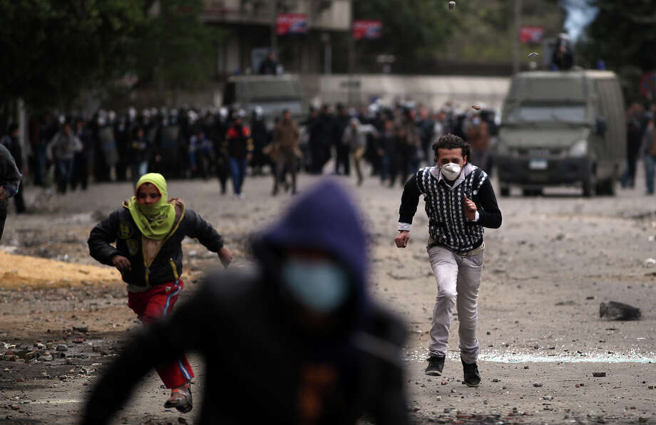 Egyptian protesters run for cover during clashes with riot police near Tahrir Square, Cairo, Egypt, Monday, Jan. 28, 2013. Health and security officials say a protester has been killed in clashes between rock-throwing demonstrators and police near Tahrir Square in central Cairo. The officials say the protester died Monday on the way to the hospital after being shot. (AP Photo/Khalil Hamra) Photo: Khalil Hamra, ASSOCIATED PRESS / AP2013