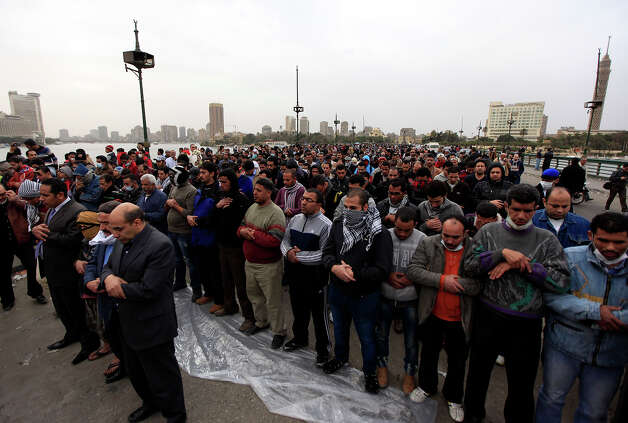 Egyptian protesters perform prayers on Qasr Al-Nile bridge leading to Tahrir Square, Cairo, Egypt, Monday, Jan. 28, 2013. Health and security officials say a protester has been killed in clashes between rock-throwing demonstrators and police near Tahrir Square in central Cairo. The officials say the protester died Monday on the way to the hospital after being shot. (AP Photo/Khalil Hamra) Photo: Khalil Hamra, ASSOCIATED PRESS / AP2013